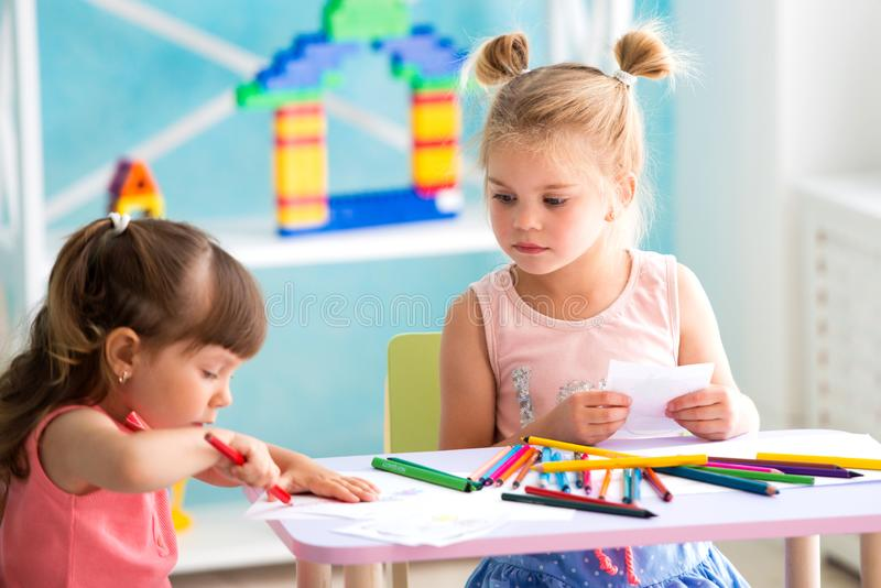 Drenaje hermoso de dos peque?o muchachas con los l?pices coloridos foto de archivo libre de regalías