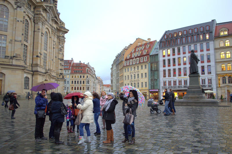 Tourists sightseeing on rainy Dresden street royalty free stock photography