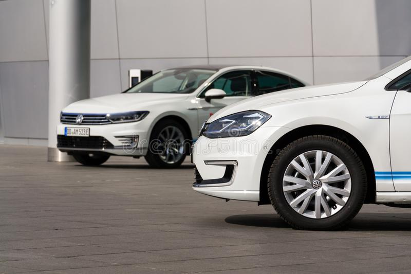 Plug-in hybrid Volkswagen Golf GTE and e-Golf electric cars stand by charging station in front of the Glaserne Manufaktur stock image