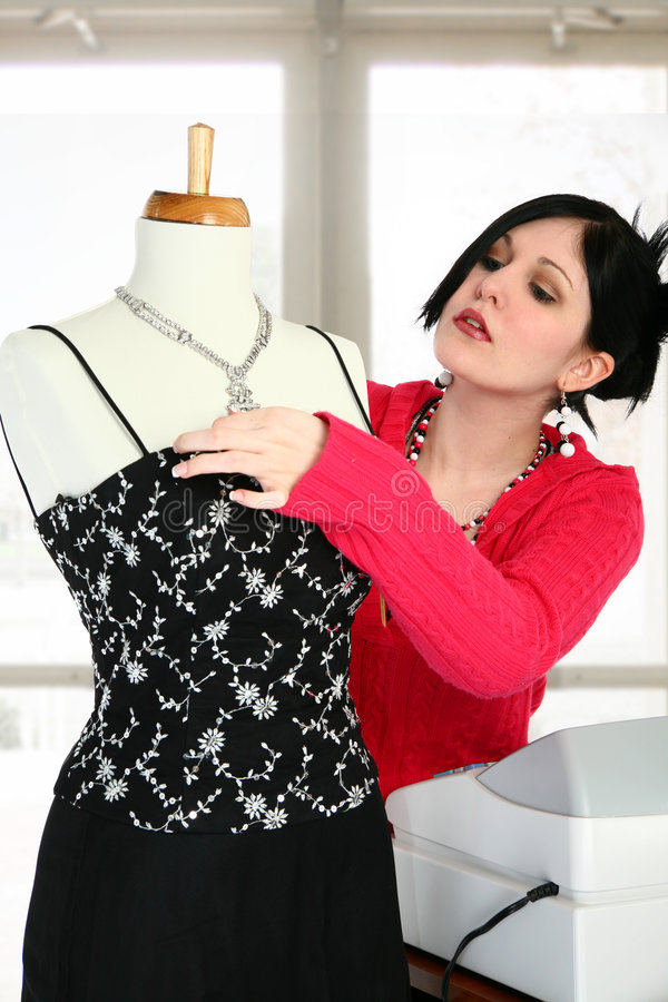 Dress Shop. Woman adjusting mannequin in dress shop