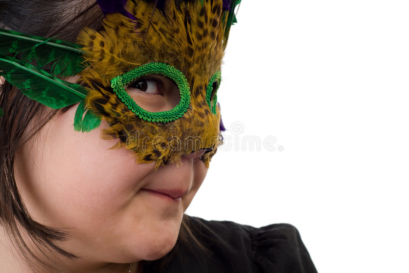 Dress-up. Closeup of a young girl playing dress-up and wearing a feather mask, isolated against a white background royalty free stock image