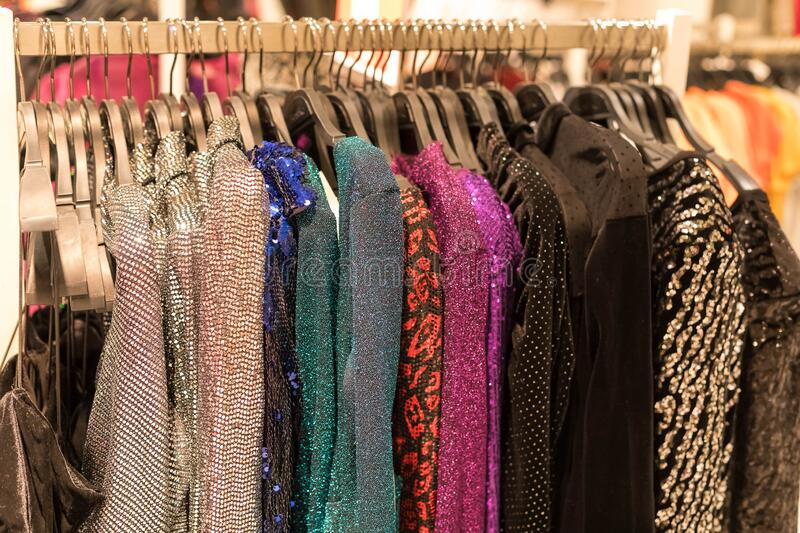 Dress-up, festive women `s clothes with glitter and payets on hangers in the store. Season of sale, black Friday, preparation for royalty free stock photography