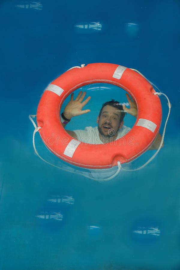 Dressed man with watch is trapped under water. He is trying to get into the lifebuoy. stock image
