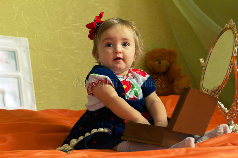 Dressed small girl plays with casket stock photos