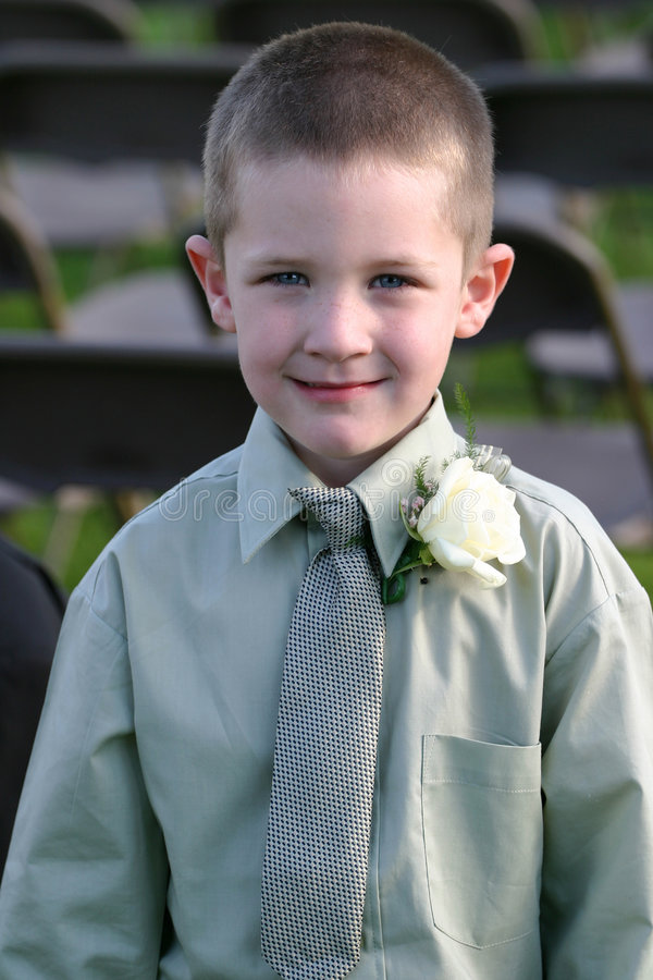 Dressed for Success. A young boy in long sleeved shirt, clip on tie (slightly off) and with a corsage cracks a nice smile. He has deep blue colored eyes and is stock photography