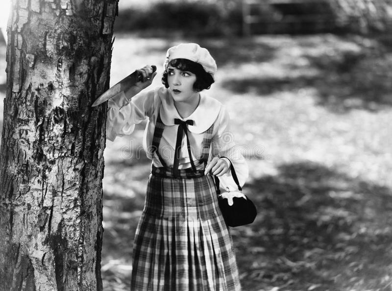 Dressed to kill, a young woman with a knife waits behind a tree stock photos