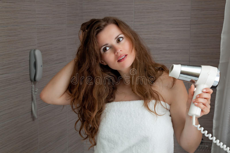 Dressed in towel beautiful woman using fen. At modern bathroom stock images