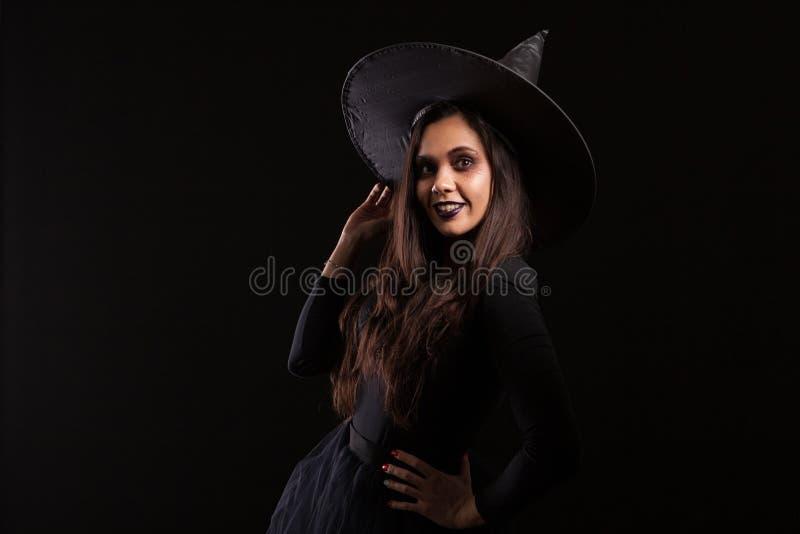 Dressedup atrativo da jovem mulher como uma bruxa para o Dia das Bruxas com um sorriso grande do chapéu imagem de stock