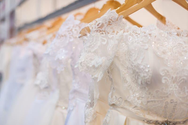 Dresses in the bridal salon. Wedding dresses hang on hangers in the bridal salon royalty free stock photos