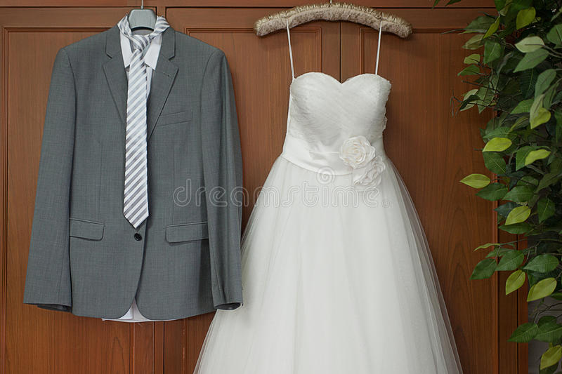 Dresses of couple. Weddinh dresses hanging on the cupboard royalty free stock photography