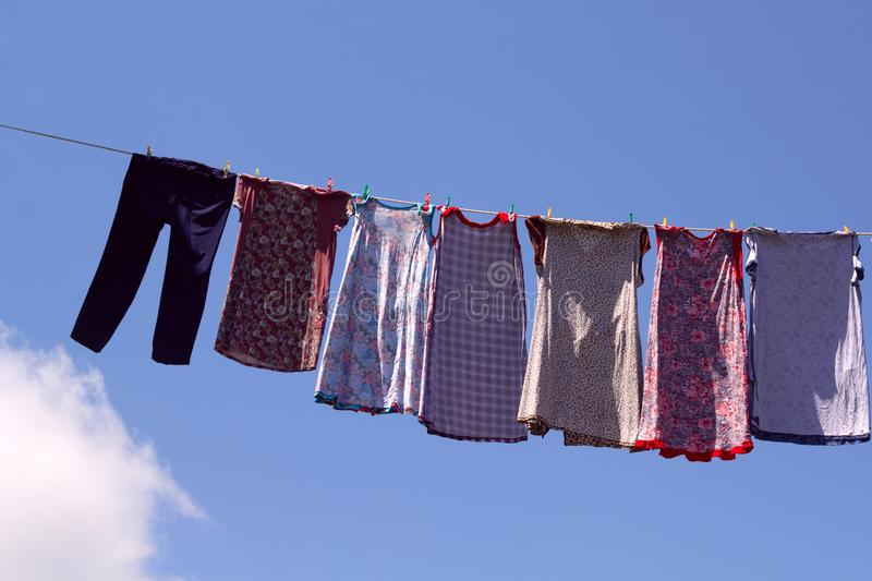 Dresses and pants hanging on a rope outside. After washing on a sunny day stock photography
