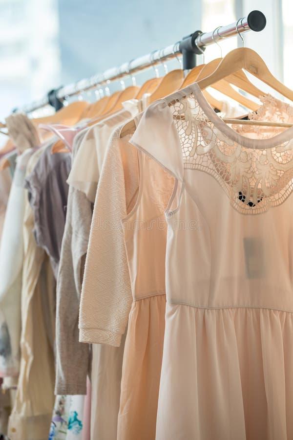 Dresses on a wooden hangers. Set of light colored dresses on a wooden hangers stock images
