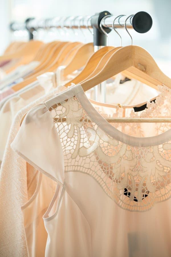Dresses on a wooden hangers. Set of light colored dresses on a wooden hangers stock image