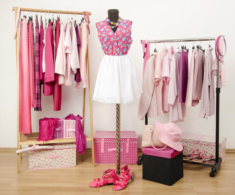 Dressing closet with pink clothes arranged on hangers and an outfit on a mannequin. royalty free stock images