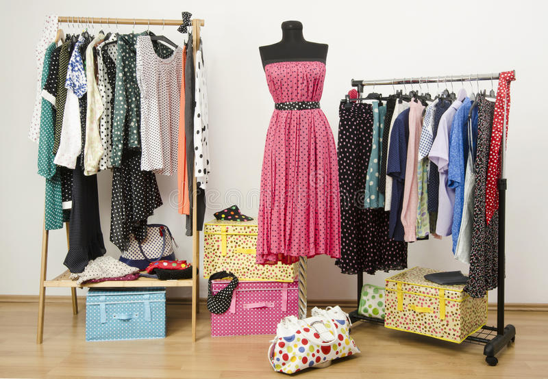 Dressing closet with polka dots clothes arranged on hangers and a dress on a mannequin. Colorful wardrobe with polka dots clothes and accessories stock photography