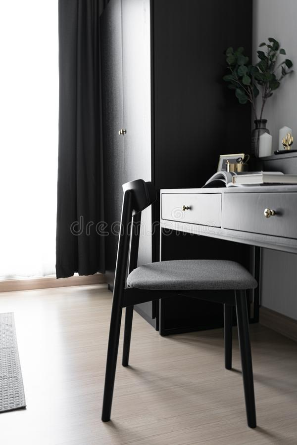 Dressing table corner with black wood power table and black wooden chair  and circular black mirror in natural light scene / cozy royalty free stock photos