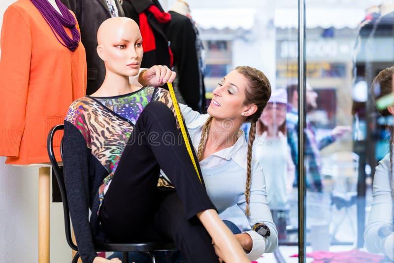 Dressingen för små och medelstora företagägaren shoppar fönstret arkivbild