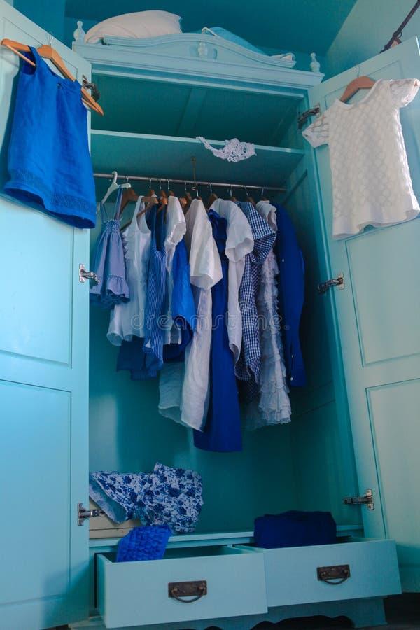 Dressinggarderob med blåttkläder i garderoben arkivbilder