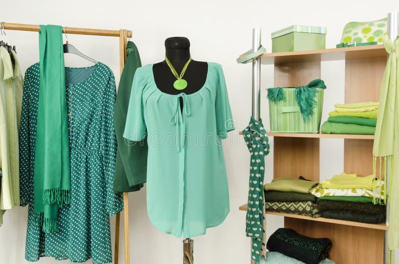 Dressinggarderob med gräsplankläder som är ordnad på hängare och hyllan, dräkt på en skyltdocka royaltyfri foto