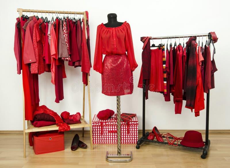 Dressinggarderob med röd kläder som är ordnad på hängare och en dräkt på en skyltdocka. royaltyfri foto