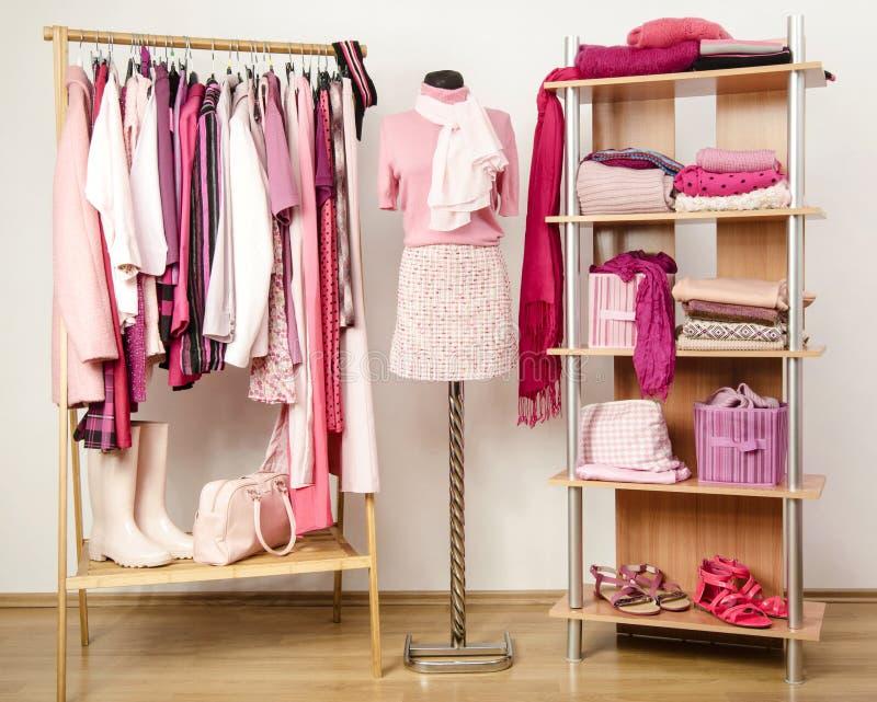 Dressinggarderob med rosa färgkläder som är ordnad på hängare och hyllan, dräkt på en skyltdocka. fotografering för bildbyråer