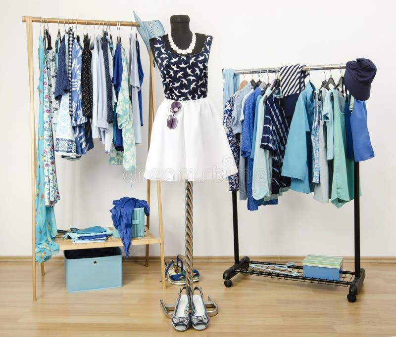 Dressinggarderoben med blått beklär ordnat på hängare. Gullig sommardräkt på en skyltdocka. arkivbilder