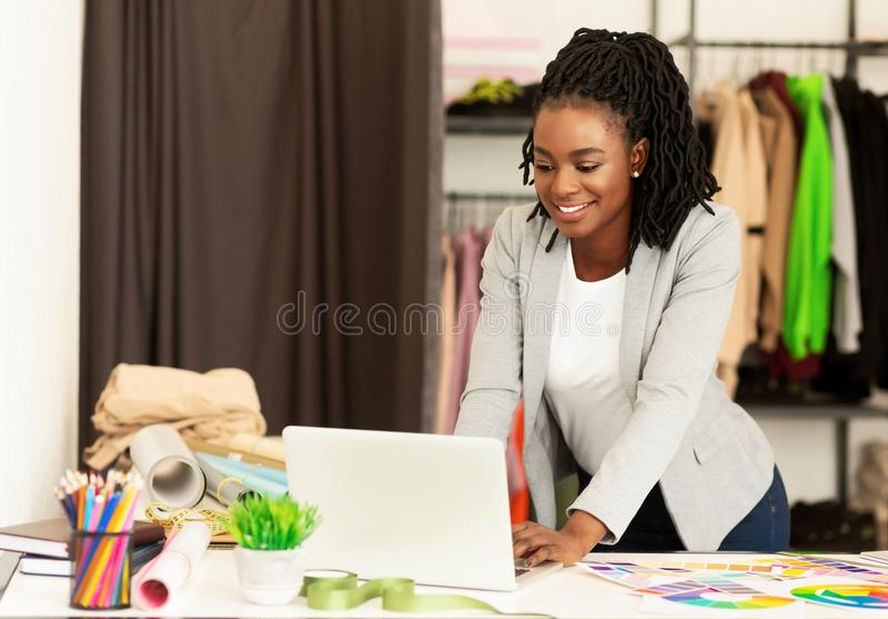 Dressmaker Africani Americani Che Lavorano Con Un Portatile In Showroom fotografia stock