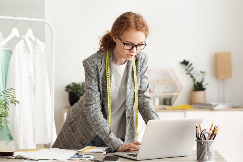 Dressmaker che utilizza un computer portatile per la raccolta di nuovi capi di abbigliamento immagini stock