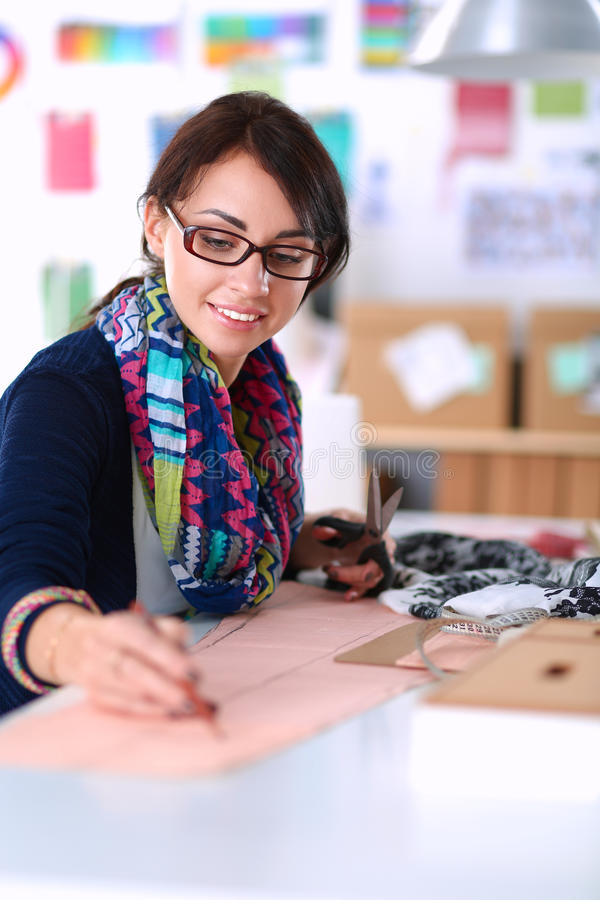 Dressmaker designing clothes pattern on paper.  royalty free stock photos