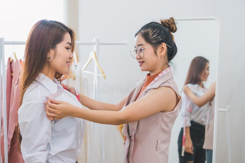 Dressmaker measuring female customer shoulder and chest in sewing atelier workshop office. Tailor and fashion designer concept. Job and freelance occupation stock image