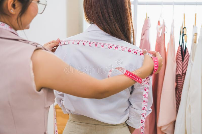Dressmaker measuring female customer shoulder in sewing atelier workshop office. Tailor and fashion designer concept. Job and. Freelance occupation. Business royalty free stock photography