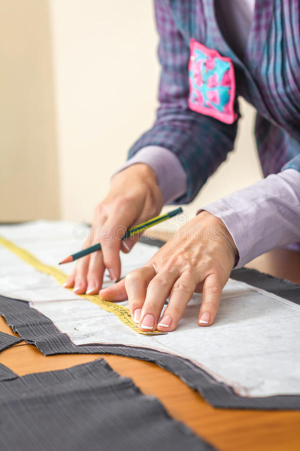 Dressmaker measuring tailor pattern on the table. Woman dressmaker measuring tailor pattern for a suit on the table royalty free stock image