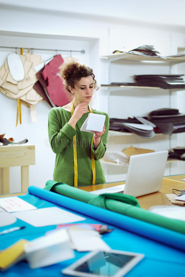 Dressmaker working in her studio with laptop and tablet stock photography