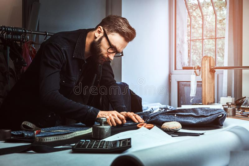 Dressmaker is working on his own project at his atelier. Dressmaker is measuring fabric  with meter  in his studio. He is wearing denim and glasses. There are a stock photo