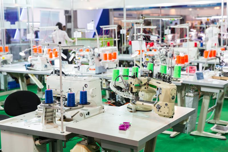 Dressmaker workplace, sewing machines on factory. Overlock machine, nobody, clothing sew on fabric. Cloth manufacturing stock images