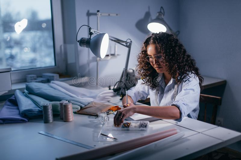 Dressmaker writing the count of beads at work royalty free stock photo