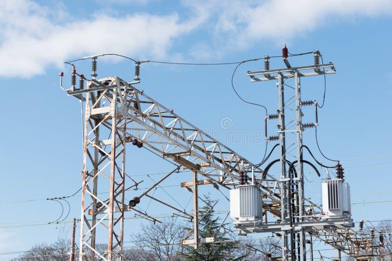 Drev- eller järnvägkraftledningservice Järnväg kraftledningar med hög spänningselektricitet på metallpoler mot blå himmel royaltyfria bilder