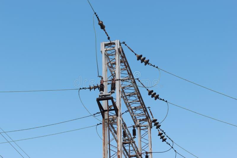 Drev- eller järnvägkraftledningservice Järnväg kraftledningar med hög spänningselektricitet på metallpoler mot blå himmel royaltyfri bild