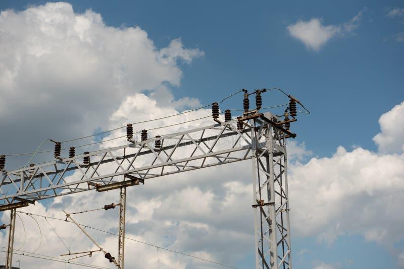 Drev- eller järnvägkraftledningservice Järnväg kraftledningar med hög spänningselektricitet på metallpoler mot blå himmel fotografering för bildbyråer