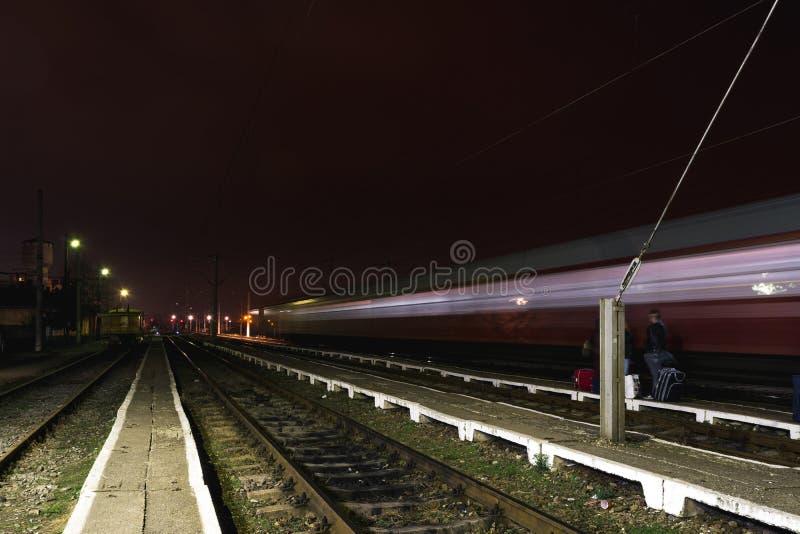 Drev som förbigår en lantlig järnvägsstation i Rumänien royaltyfri foto