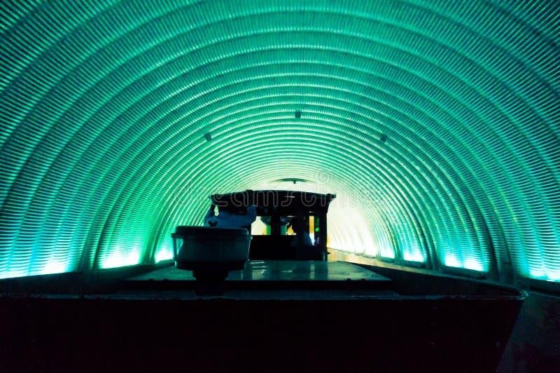 Drev som kör till och med en rund grön blå tunnel arkivfoto