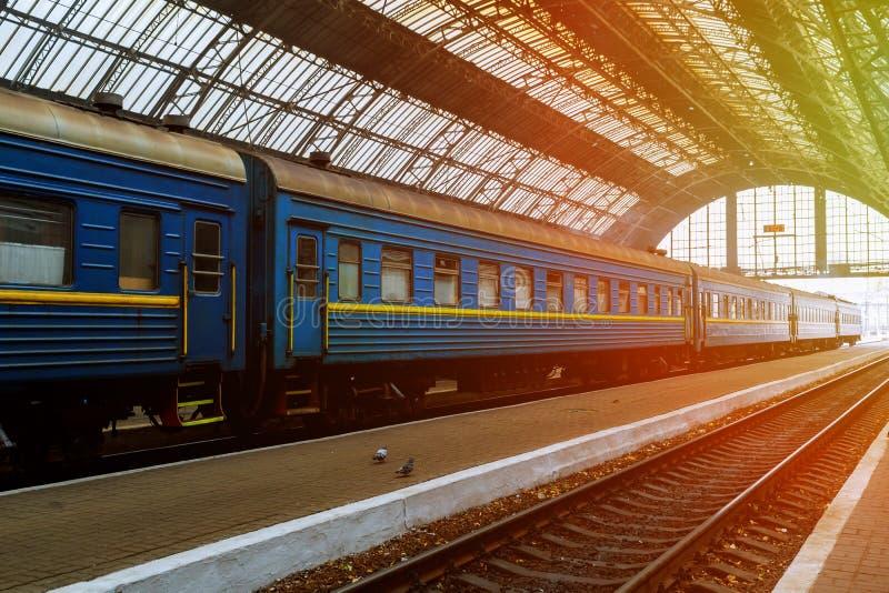 Drev står på stationen på den soluppgångtidLviv centralstationen royaltyfri fotografi