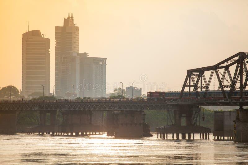 Drevet kör längs den långa Bien bron i den härliga solnedgången Hanoi, Vietnam royaltyfri foto