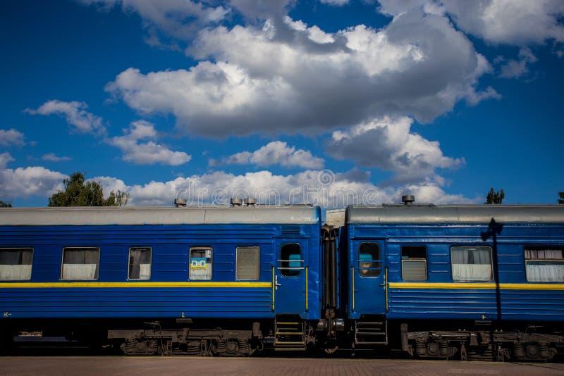 Drevet med blåa vagnar står på plattformen mot bakgrunden av en härlig sommarhimmel royaltyfri bild