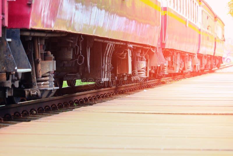 Drevhjulslut upp på järnvägsspår på stationen med den valda fokusen för solnedgångljussignal med grunt djup av fältet royaltyfri bild