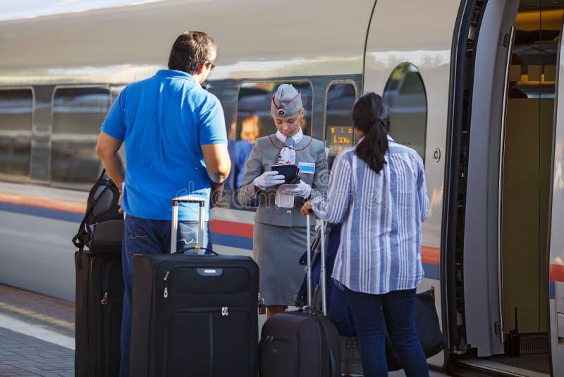 Drevlyxfnasket kontrollerar biljetterna och dokumenten, medan stiga ombord det snabba elektriska drevet Sapsan moscow russia arkivbild