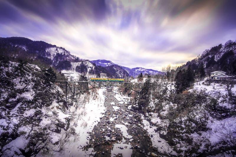 Drevrutten från den Chigaki stationen har täckt snö i vinter Järnväg Tateyama för Toyama region som linje korsar järnbrovad royaltyfria bilder