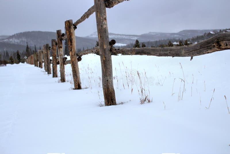 Drewna ogrodzenie w śniegu fotografia stock