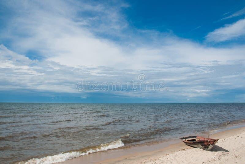 Drewniana łódź na piaskowatym brzeg jeziorny Baikal, niebieskie niebo i spokój woda, obraz royalty free