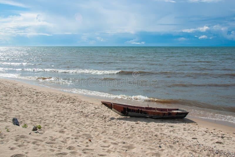 Drewniana łódź na piaskowatym brzeg jeziorny Baikal, niebieskie niebo i spokój woda, zdjęcie royalty free